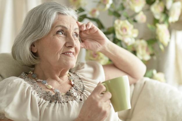 Happy senior woman resting à la maison avec une tasse de thé