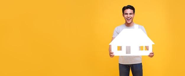 Happy smiling asian man holding paper home isolé sur fond jaune avec copie espace. fond panoramique.