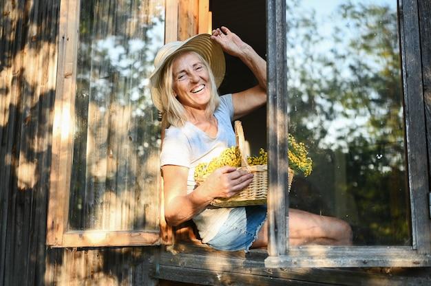 Happy smiling femme senior émotionnelle posant par fenêtre ouverte dans la vieille maison de village en bois en chapeau de paille avec panier de fleurs