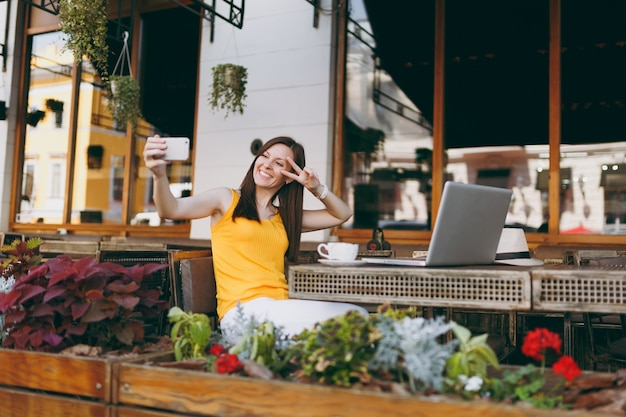 Happy smiling girl in outdoor street coffee shop café assis à table avec un ordinateur portable en prenant selfie shot sur téléphone mobile au restaurant pendant le temps libre