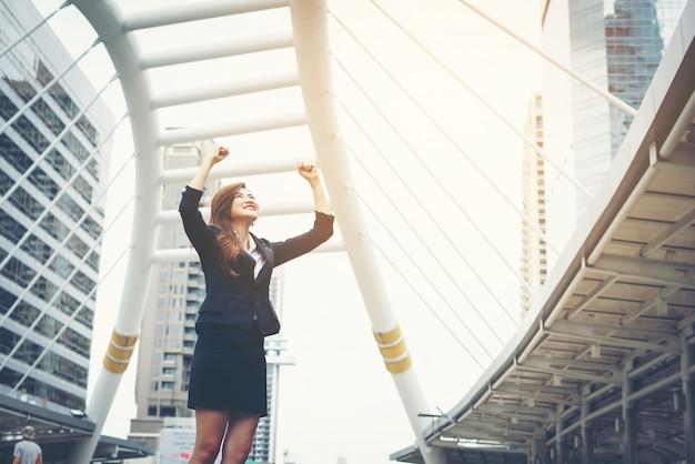 Happy success businesswoman dominant les mains du centre-ville.