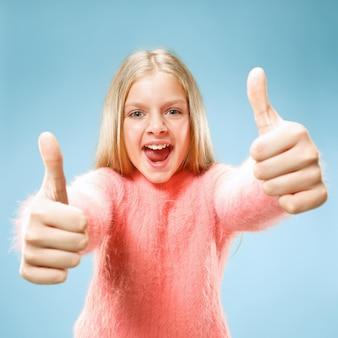 Happy teen girl debout, souriant isolé sur fond de studio bleu à la mode. beau portrait féminin. jeune fille satisfaite avec signe ok.