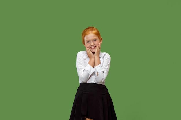 Happy teen girl debout, souriant isolé sur fond de studio vert branché.