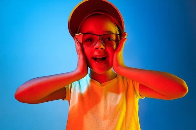 Happy teen girl debout et souriant isolé sur studio néon bleu branché