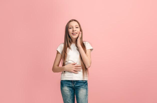 Happy teen girl debout, souriant isolé sur un studio rose à la mode
