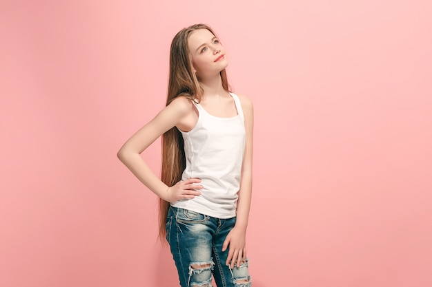 Happy teen girl debout, souriant isolé sur un studio rose à la mode.