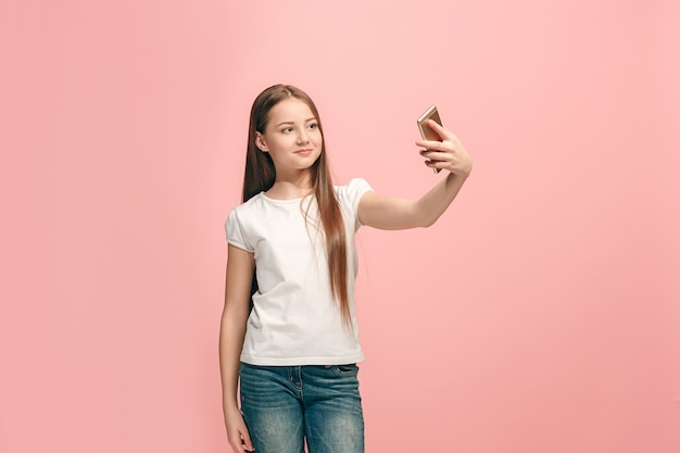 Happy teen girl debout, souriant sur studio rose