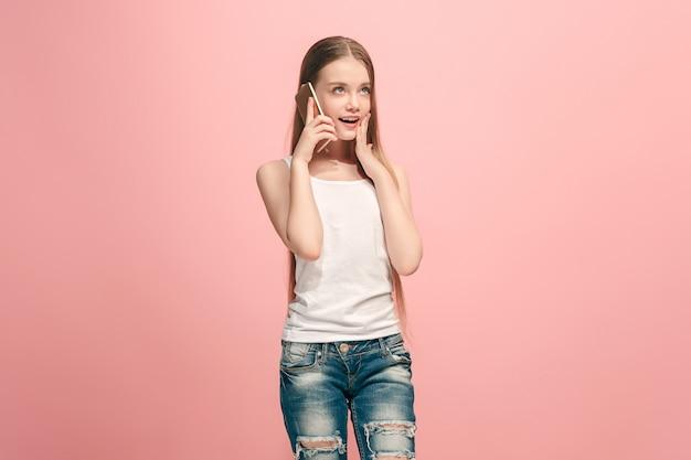 Happy teen girl debout, souriant avec un téléphone mobile sur fond de studio rose à la mode. beau portrait de femme demi-longueur. émotions humaines, concept d'expression faciale.