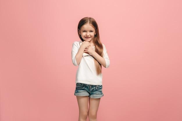 Happy teen girl debout, souriant avec un téléphone mobile sur un mur rose à la mode. beau portrait de femme demi-longueur. émotions humaines, concept d'expression faciale.