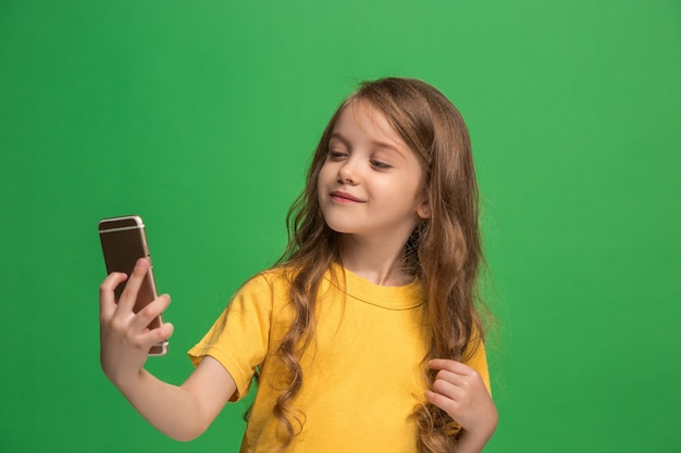 Happy teen girl debout, souriant avec un téléphone mobile sur un mur de studio vert à la mode