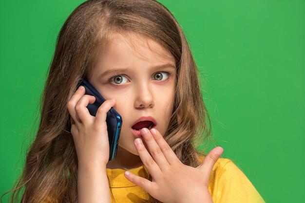 Happy teen girl debout, souriant avec un téléphone mobile sur un mur vert à la mode. beau portrait de femme demi-longueur. émotions humaines, concept d'expression faciale.
