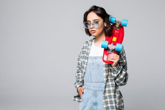 Happy teen girl holding skate board isolé