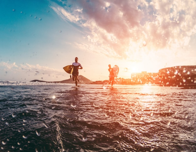 Happy urfers courir avec des planches de surf sur la plage