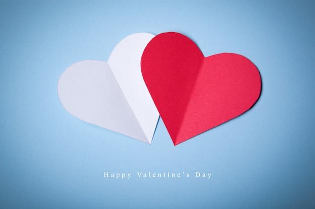 Happy valentines day, coeurs rouges et blancs de papier sur fond bleu. bonne carte de vacances.