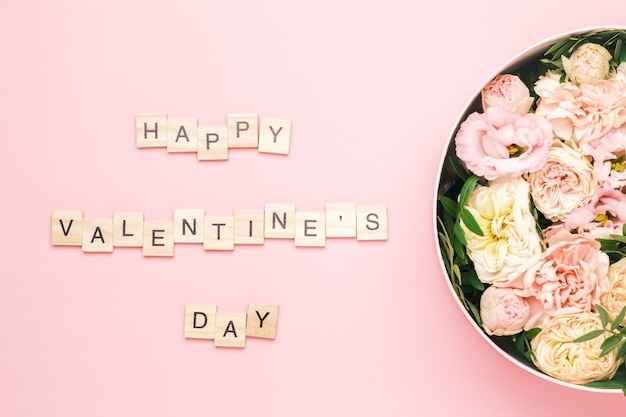 Happy valentines day sur fond rose avec une boîte ronde de chapeau avec des fleurs dans le coin.