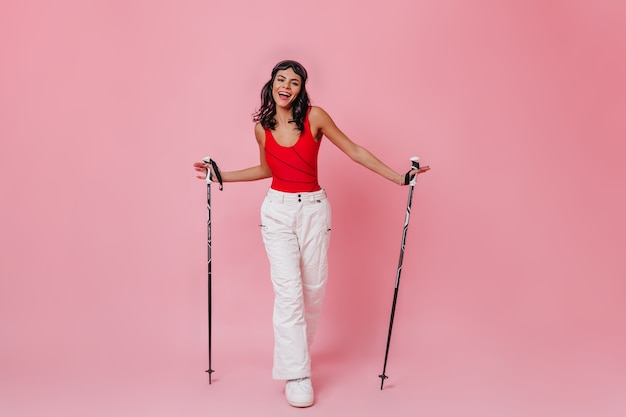 Happy woman holding bâtons de ski sur fond rose