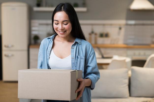 Happy woman holding box avec commande en ligne