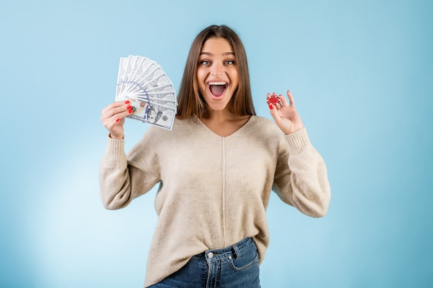 Happy woman holding casino poker chip et dollars d'argent isolé sur bleu