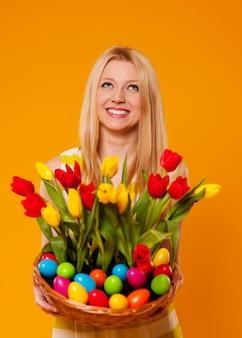 Happy woman holding panier avec fleur de printemps et oeufs de pâques