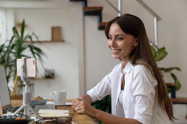 Happy woman looking at mobile phone sur trépied ayant un appel vidéo en ligne