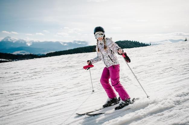 Happy woman ski dans les montagnes enneigées