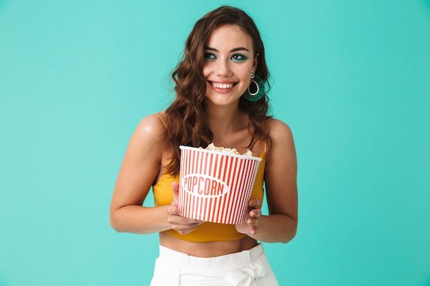 Happy woman wearing fashion earrings holding bucket avec pop-corn et souriant