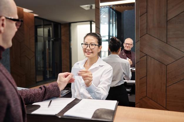Happy young businesswoman in formalwear prenant la carte de la chambre d'hôtel après avoir rempli le formulaire par le comptoir de la réception