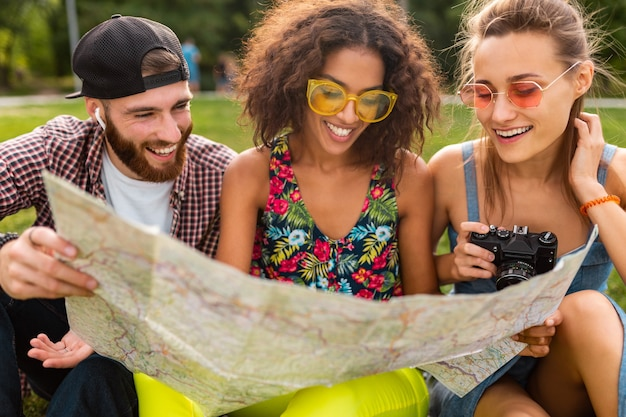 Happy young company of friends sitting park voyageant à la recherche de visites de la carte, l'homme et la femme s'amusant ensemble