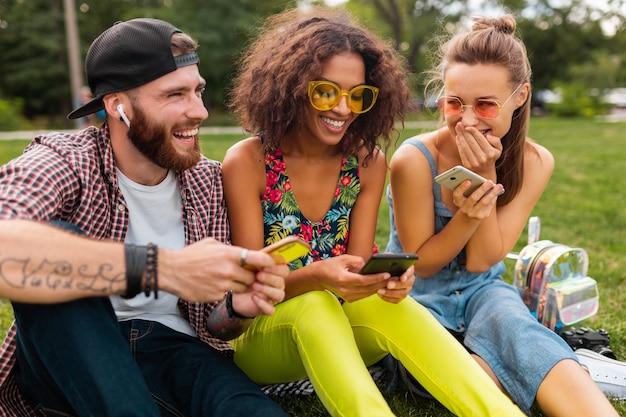 Happy young company of smiling friends sitting park à l'aide de smartphones, homme et femme s'amusant ensemble