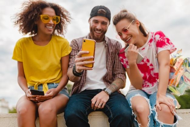 Happy young company of smiling friends sitting park à l'aide de smartphones