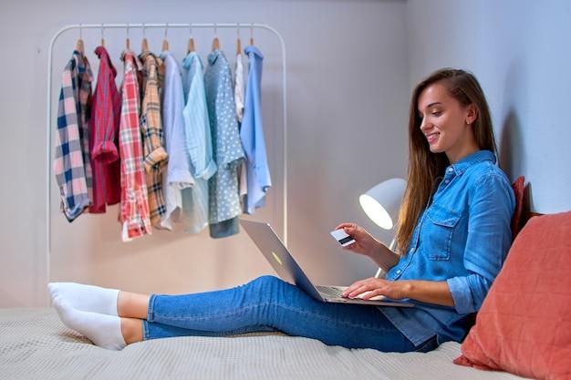 Happy young girl shopper shopaholic shopping en ligne et payer des biens et des achats en utilisant une carte de crédit et un ordinateur portable. e-commerce et style de vie moderne