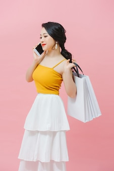 Happy young woman holding shopping bags et téléphone mobile sur fond blanc