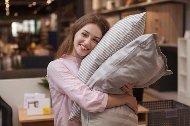 Happy young woman hugging oreillers, shopping pour la maison au grand magasin