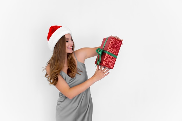 Happy young woman in santas hat lève le présent tandis que se dresse sur fond blanc célébration