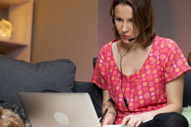Happy young woman wear headset communicating by conference call speak looking at computer at home