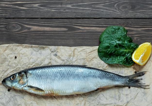 Un hareng atlantique salé entier sur du papier sulfurisé, à côté d'épices, de citron et de feuille de laitue