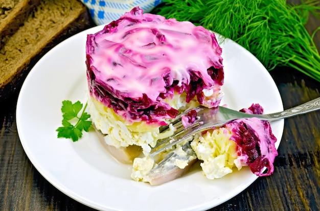 Hareng aux légumes dans une assiette blanche avec une fourchette, persil, aneth, pain, serviette sur fond de planches de bois