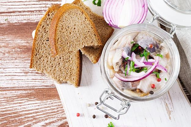 Hareng mariné dans un bocal avec des oignons. nourriture scandinave.