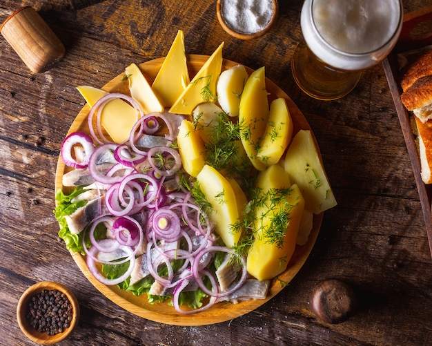Hareng avec pommes de terre à l'oignon, beurre et légumes verts servis avec de la bière 1
