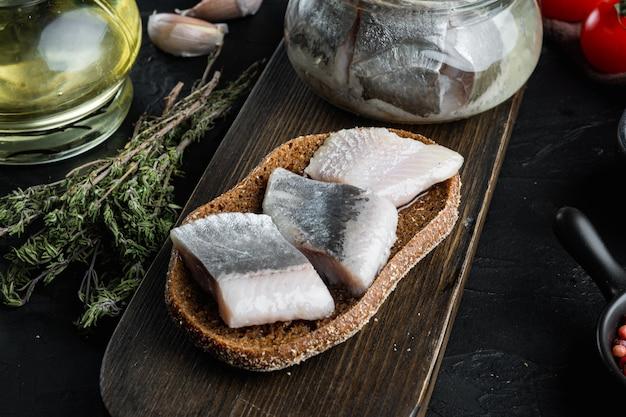 Hareng sauvage de l'atlantique, conserves de poisson en conserve marinées, sur une planche à découper en bois, sur un tableau noir avec des herbes et des ingrédients