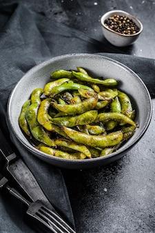 Haricot edamame cuit à la vapeur, soja vert dans une poêle, cuisine asiatique. fond blanc. vue de dessus.