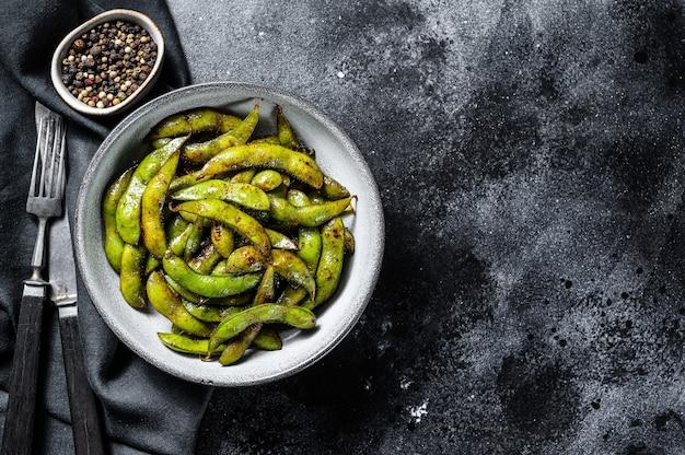 Haricot edamame cuit à la vapeur, soja vert dans une poêle, cuisine asiatique. fond blanc.