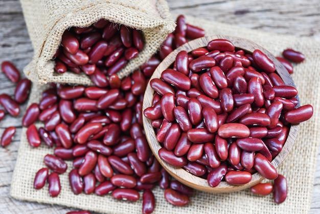 Haricot rouge dans un bol en bois sur fond de sac / grains de haricots rouges