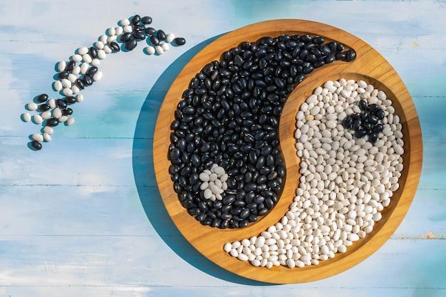 Haricots sur une assiette yin et yang aliments sains protéine vue de dessus sur un fond en bois