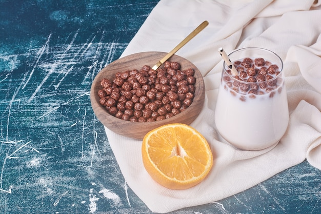 Haricots au chocolat avec une tasse de lait sur bleu.