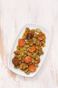 Haricots aux saucisses fumées sur plat blanc