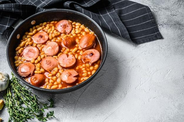 Haricots aux saucisses à la sauce tomate dans une casserole. fond blanc. vue de dessus. copiez l'espace.