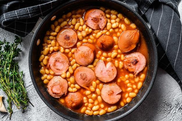 Haricots aux saucisses à la sauce tomate dans une casserole. vue de dessus.