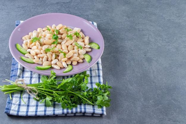 Haricots blancs au concombre sur une assiette à côté du brunch de persil sur une serviette, sur le fond de marbre.