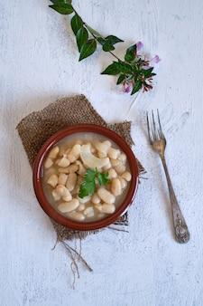 Haricots blancs cuits uniquement avec de l'oignon dans un pot en argile. nourriture propre et saine